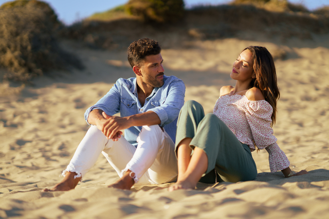 couple sitting on the sand of the beach